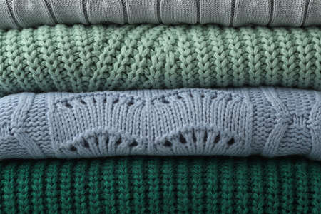 Stack of warm clothes as background, closeup. Autumn season