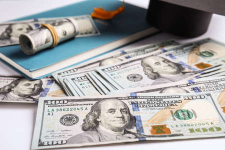 Dollars with student graduation hat and book on white background. Tuition fees concept