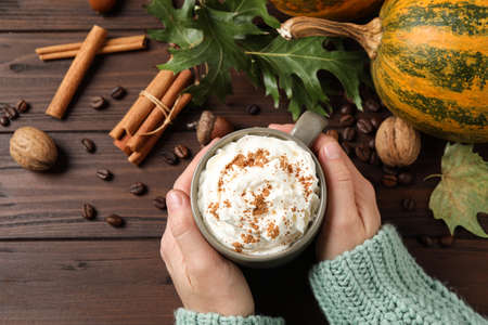 Woman with cup of tasty pumpkin spice latte at wooden table, top view