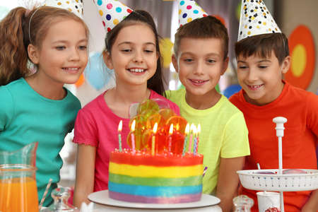 Children near cake with candles at birthday party indoors
