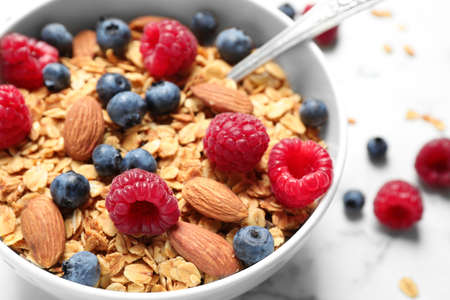 Tasty homemade granola with berries on white marble table, closeup. Healthy breakfast Stok Fotoğraf