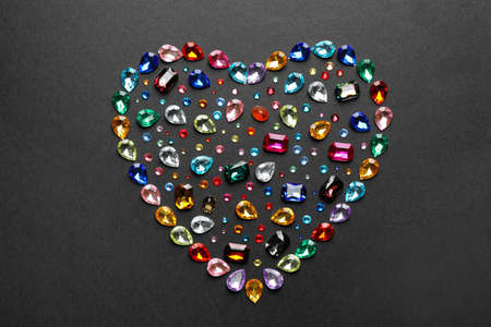 Heart shaped pile of different beautiful gemstones on black background, flat lay Banco de Imagens