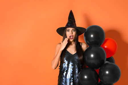 Surprised woman wearing witch costume with balloons for Halloween party on yellow background, space for text