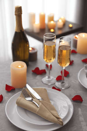 Romantic table setting with burning candles and rose petals indoors