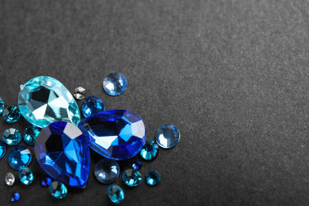 Pile of different beautiful gemstones on black background. Space for text Stock Photo