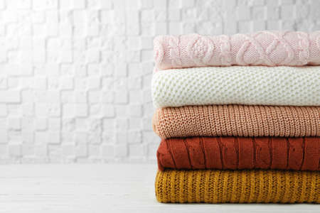 Stack of warm clothes on white wooden table against textured wall, space for text. Autumn season
