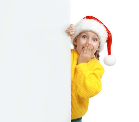 Emotional child in Santa hat peeping out of blank banner on white background. Christmas celebration 写真素材