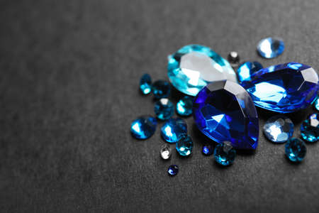 Pile of different beautiful gemstones on black background. Space for text Banco de Imagens