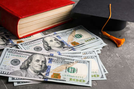 Dollars, student graduation hat and book on stone background. Tuition payments concept