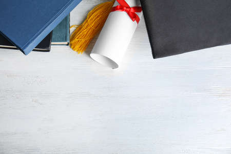 Flat lay composition with graduation hat and student's diploma on white wooden table, space for text Standard-Bild