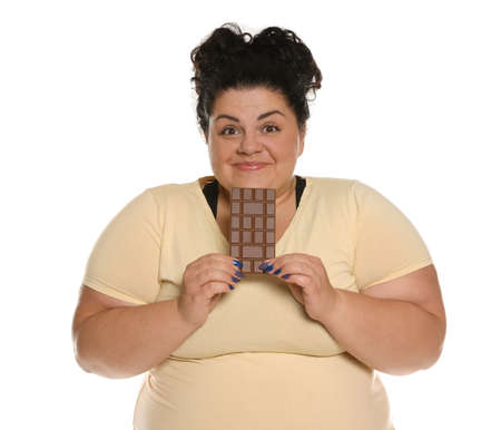 Happy overweight woman with chocolate on white background Banco de Imagens