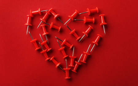 Heart shaped pile of pins on red background, flat lay