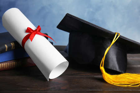 Graduation hat, books and students diploma on black wooden table against light blue background