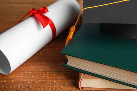 Graduation hat, books and students diploma on wooden table, closeup Reklamní fotografie