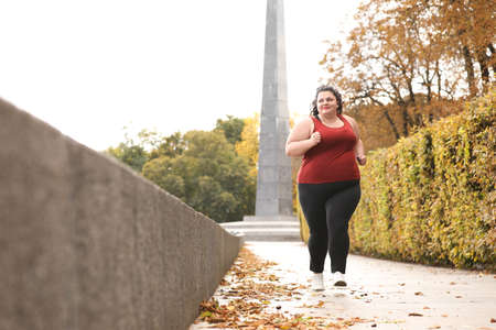 Beautiful overweight woman running in park. Fitness lifestyle