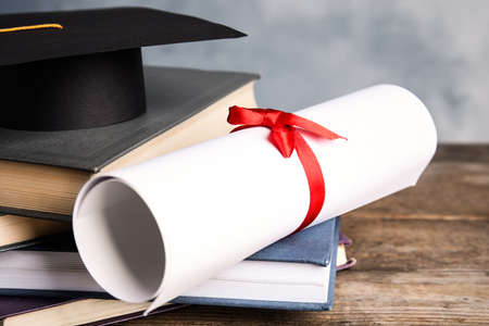 Graduation hat, books and students diploma on wooden table Reklamní fotografie