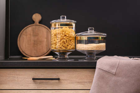 Raw cereals on black table in modern kitchen
