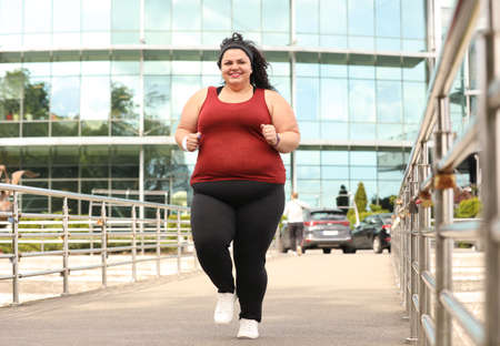 Beautiful overweight woman running outdoors. Fitness lifestyle