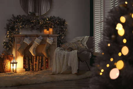 Fireplace with Christmas stockings in festive room interior Stock Photo
