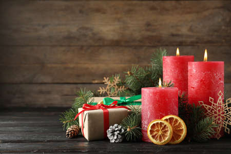 Beautiful Christmas composition with burning red candles on wooden background. Space for text