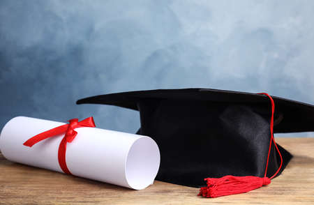 Graduation hat and students diploma on wooden table against light blue background