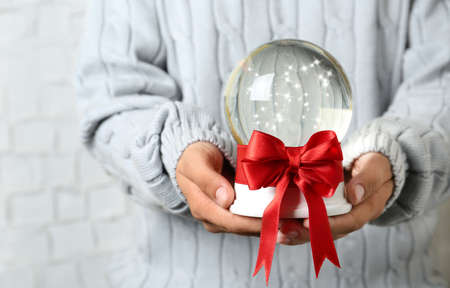 Woman holding snow globe with red bow on blurred background, closeup