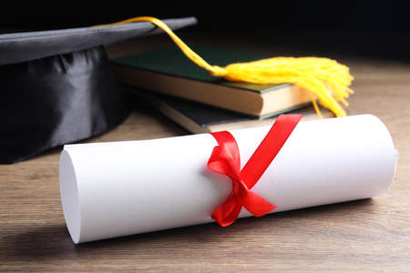 Graduation hat, books and students diploma on wooden table 스톡 콘텐츠