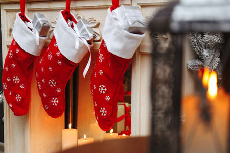 Fireplace with Christmas stockings in festive room interior Banco de Imagens