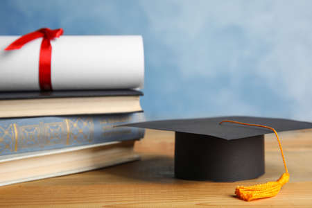 Graduation hat, books and students diploma on wooden table against light blue background