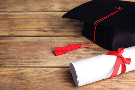Graduation hat and student's diploma on wooden table, space for text Stock fotó