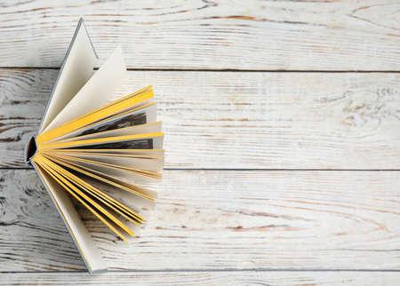 Libro con copertina rigida su fondo di legno bianco, vista dall'alto. Spazio per il testo