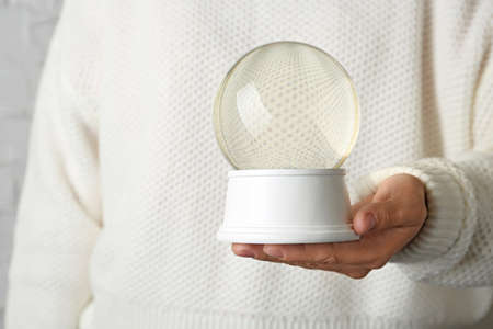 Woman wearing white sweater holding empty snow globe, closeup 版權商用圖片