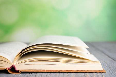 Offenes Buch auf grauem Holztisch gegen unscharfen grünen Hintergrund, Nahaufnahme. Platz für Text