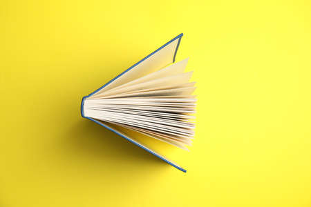 Hardcover book on yellow background, top view Stok Fotoğraf