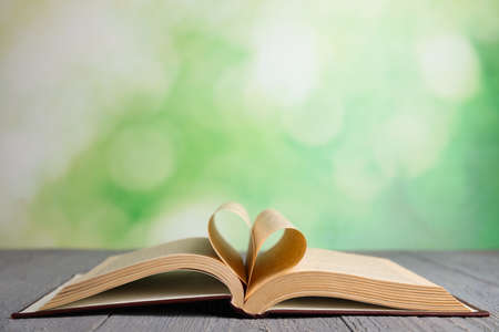 Open book on grey wooden table against blurred green background. Space for text