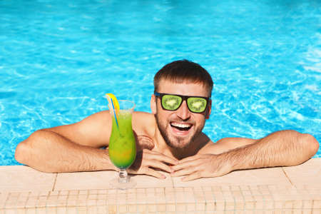 Young man with cocktail in swimming pool on sunny day. Fruit sunglasses as summer trend