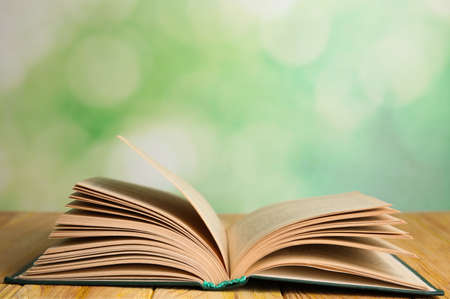 Open book on wooden table against blurred green background. Space for text