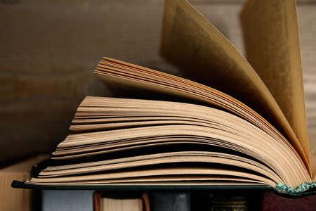 Open hardcover book near wooden background, closeup