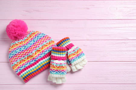 Warm knitted hat and mittens on pink wooden background, flat lay. Space for text Foto de archivo