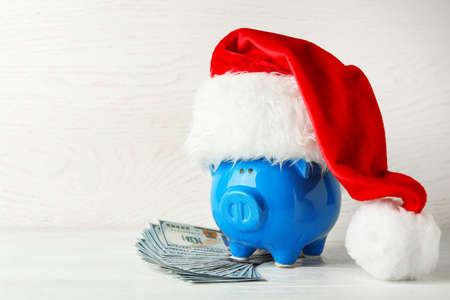 Salvadanaio con cappello da Babbo Natale e banconote in dollari sul tavolo di legno bianco. Spazio per il testo