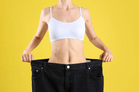 Young slim woman wearing oversized jeans on yellow background, closeup Reklamní fotografie
