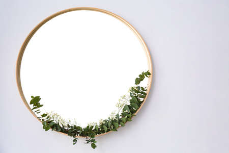 New round mirror in wooden frame on white wall, space for text. Idea for interior design