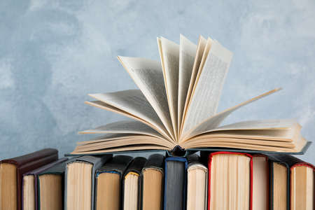 Stack of hardcover books on light blue background