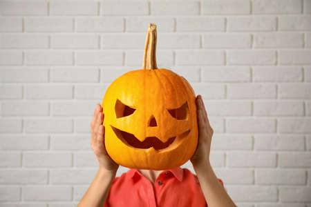 Woman with pumpkin head near white brick wall. Jack lantern - traditional Halloween decor Imagens