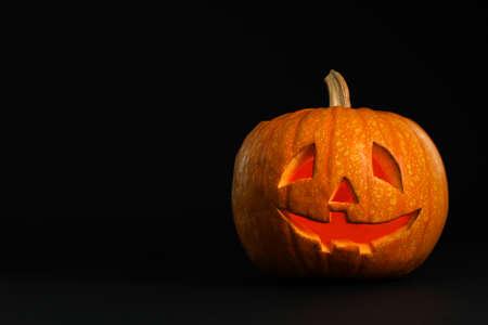 Pumpkin head on black background, space for text. Jack lantern - traditional Halloween decor