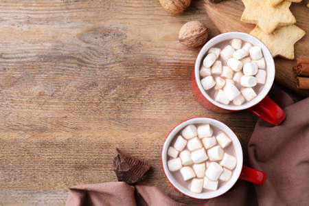 Flat lay composition of tasty cocoa with marshmallows on wooden table. Space for text Zdjęcie Seryjne