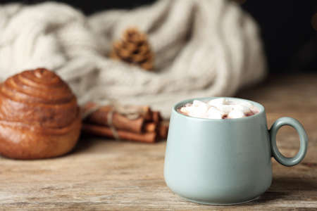 Delicious cocoa drink with marshmallows in cup on wooden table, space for text