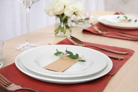Elegant festive table setting with blank card in restaurant