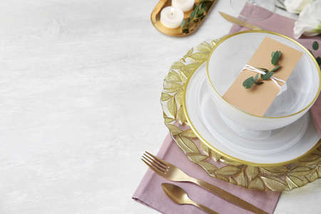 Elegant festive table setting on light background, space for text