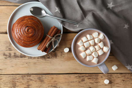 Composition with delicious hot cocoa drink and bun on wooden background, flat lay